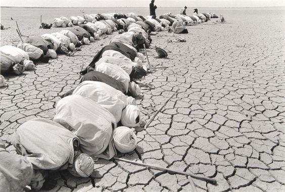 Sebastiao Salgado Mali (men kneeling in desert) 1985