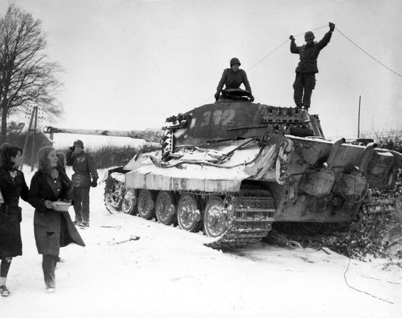 U.S. Army paratroopers of the 82nd Airborne Division inspect a destroyed German Tiger II heavy tank as Belgian women pass by with the offering of a hot meal. Corenne, Namur, Wallonia,...