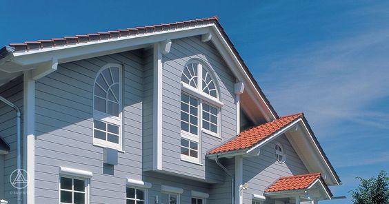 Architektur im Landhaus-Stil American Dream - Charakteristisch sind die herrliche Rundum-Veranda und die unterschiedlichen, verspielt-romantischen Glas- und Fensterelemente. Baufritz Landhaus