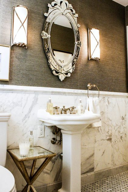 Elegant mirror hangs above the guest bathroom's pedestal sink. Modern sconces give the space a timeless feel.