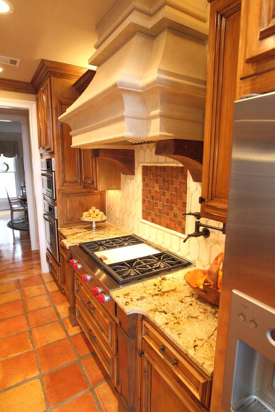 Gorgeous stone hood Handmade copper tiles and a potfiller spout in the backsplash. Mexican floor tiles and Mexican cream tiles in backsplash