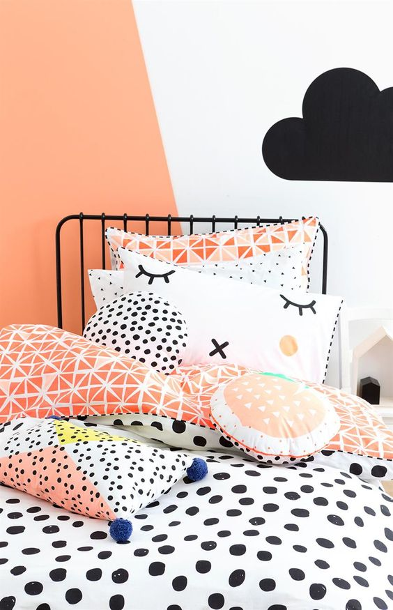 pops of peach/apricot/fruit salad on the walls and bold, playful prints in this black and white kids room