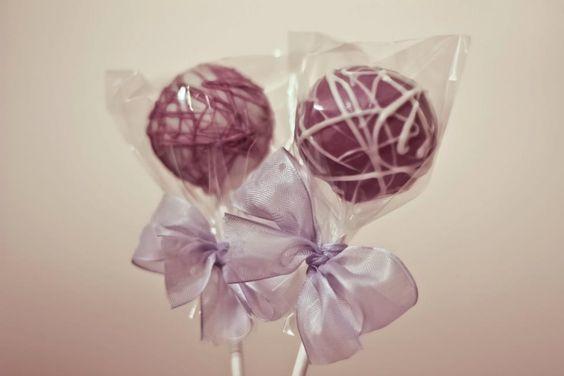 Chocolate cake pops with purple coating and white swirls.