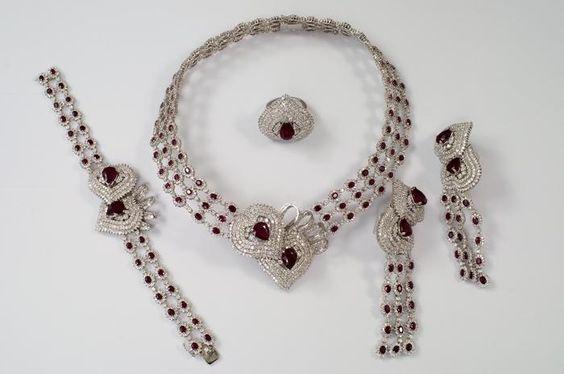 Um parure rubi e diamante impressionante que consiste em colar, pulseira, anel e brincos, fixado em ouro branco 18 quilates, o colar formado de cento e dois clusters de rubi e diamantes dispostos em três linhas e duas set diamante corações levantados cada um com pêra central de forma ruby , a pulseira combinando, anel e brincos de banho. Os rubis tratada térmico e vidro cheio. (5) - Preço Estimado: £ 8000 - £ 10000