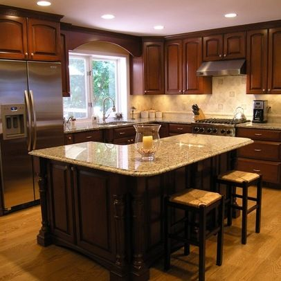 The dark cabinets here have an L shape but there's also a large island in the middle to provide more surface. You will have no problem getting to everything you want and putting it all away.