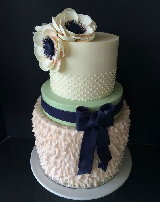 Loving the preppy feel of this mint and navy wedding cake with bow and ruffles. | See more lovely mint green #wedding details here: http://www.mywedding.com/articles/mint-wedding-details/