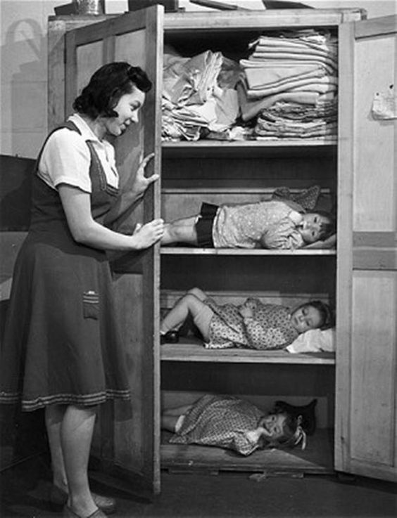 Cupboard Shelter, December 1943. A day nursery in the East End of London shelters children in a linen cupboard during an air raid.