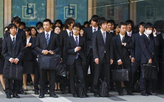 Salarymen in suits - Japanese businessmen on the sidewalk