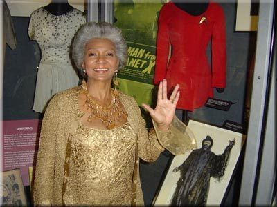 Nichelle Nichols does the Vulcan salute, next to her TOS costume.:
