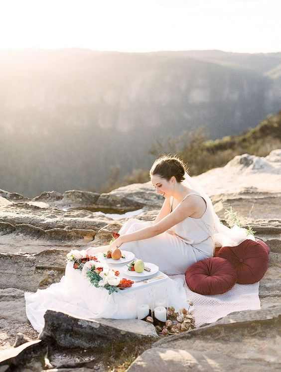 Romantic wedding picnic setting for a mountain elopement with burgundy cushions and table topped with fresh flowers and fruit   We Are Origami