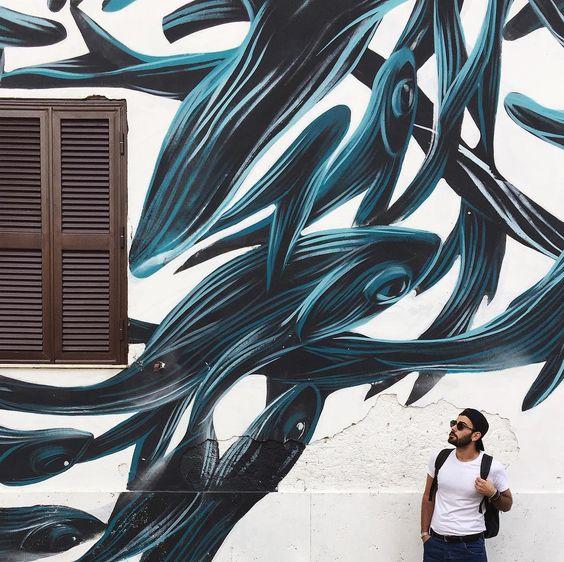 """{Street}  L'altro giorno ho avuto finalmente possibilità di vedere questo spettacolo di street art che si trova nei pressi  di Tormarancia una zona di Roma.  Sono stati in 20 artisti provenienti da diversi paesi a dipingere ben 11 palazzine.  Questa è la mia preferita e qui stavo osservando con sguardo titubante  il """"perché"""" di quella finestra messa lì a deturpare questo capolavoro mitologico di orche stilizzate  che si ergono su di me e sul mio cappello Vans by @footlockerEU   In ogni caso…"""