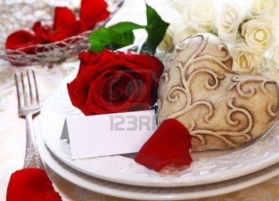 Lugar de la boda Configuración con una tarjeta de lugar, rosas rojas y blancas y un corazón Foto de archivo