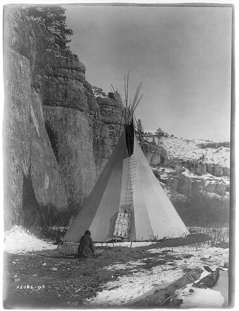 Curtis Edward  Apsaroke woman stretching hide that has been secured to the ground by stakes, tipi in background, cliff on left 1908