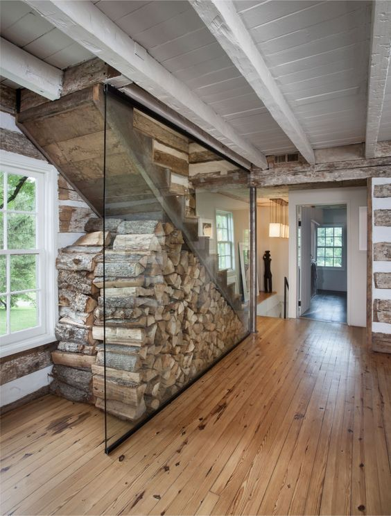 Bushman Dreyfus Architects gave the stairs to the attic of this 1780s log cabin a modern makeover that included a glass encasement to store fire wood. The firm submitted the project to Remodelista Considered Design Awards 2017. See Heirloom Farm Cottage Renovation. #Design