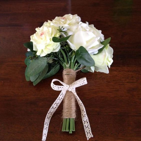 To create this look start with a pre-made bouquet. Next using natural jute cord wrap around the stems and tie at top and bottom. Finish with a simple bow of crochet lace ribbon.