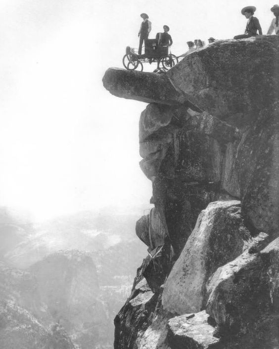 Locomobile steam car on Overhanging Rock in 1900. This was the first automobile to enter Yosemite Valley. Oliver Lippincott drove up the steep, winding road to Glacier Point. The next morning it was hauled onto Overhanging Rock by ropes for this famous photograph.