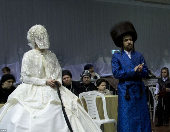 The bride holds a gartel while family members dance and thegrandson of the Rabbi of the Tzanz Hasidic dynasty wore a tile-print robe