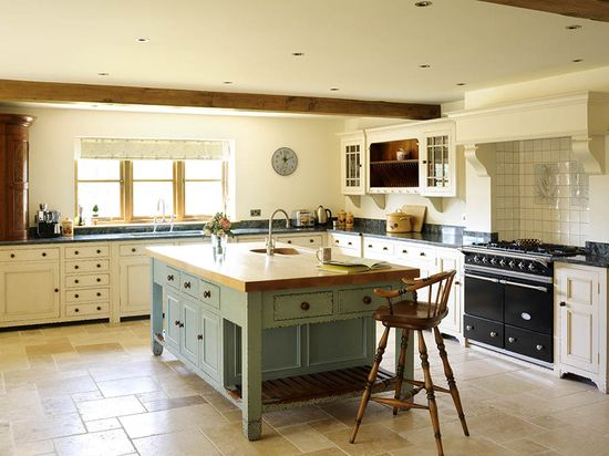 Cream kitchen cabinets with dark handles, green granite worktops