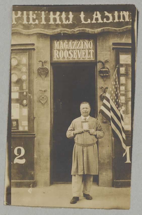 Roosevelt look-alike Pietro Casini, an Italian merchant. Casini stands outside his Magazzino Roosevelt shop in Florence, Italy, holding a U.S. flag and a photo of Roosevelt. Oct. 26, 1915. George Grantham Bain Collection, Library of Congress Prints and Photographs Division. via Pinterest