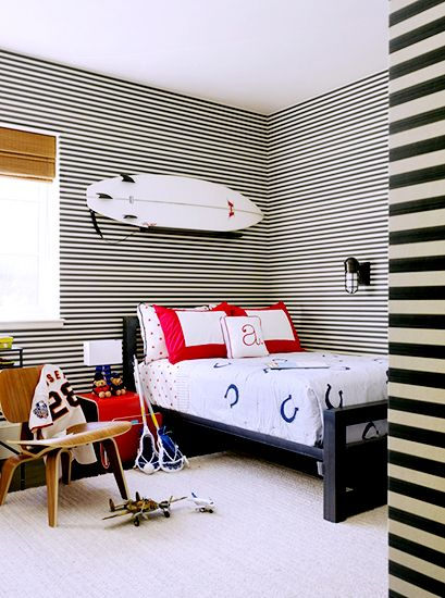 21 Homes That Prove Surf Is Chic // surfboards as decor // boy's bedroom, horizontal striped wallpaper, woven blinds, Eames Lounge Chair, horseshoe bedding