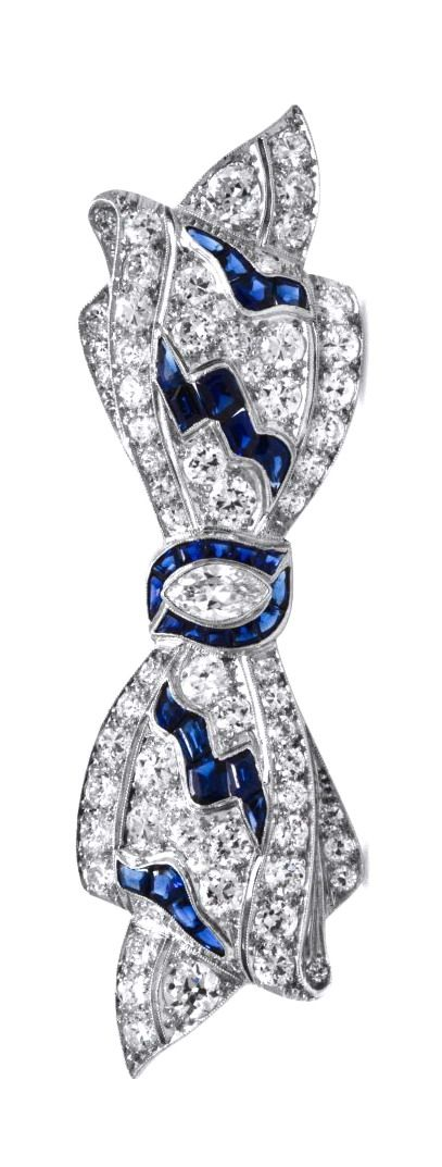 An Art Deco Platinum, Diamond and Sapphire Bow Brooch, containing one antique marquise cut diamond weighing approximately 0.32 carat, numerous old European cut diamonds weighing approximately 4.26 carats total and 30 calibre cut sapphires. Hand Inscribed: 25454.