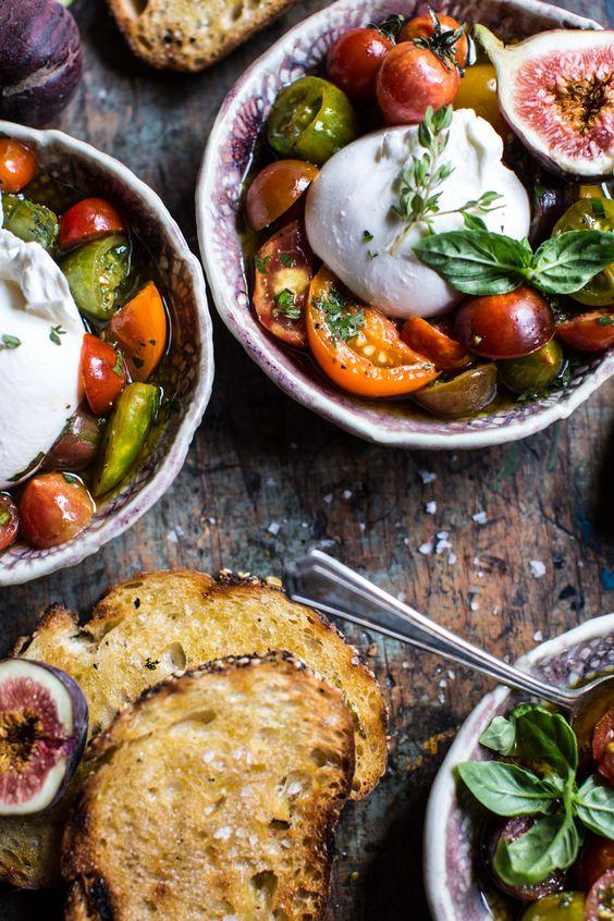 Schneiden Sie verschiedene Tomaten in Stücke und halbieren Sie Feigen. Hacken Sie Basilikum, Petersilie und ein wenig Oregano. Nun mischen Sie Zitronensaft mit Honig, geben ein wenig weissen Balsamico dazu und gutes, fruchtiges Olivenöl. Mischen Sie die gehackten Kräuter dazu und vermischen dann die Sauce mit den Tomaten und würzen mit Meersalz. Legen Sie auf jede Portion Tomatensalat eine Burrata und dekorieren mit einigen Kräutern. Mit Knoblauchbrot servieren.