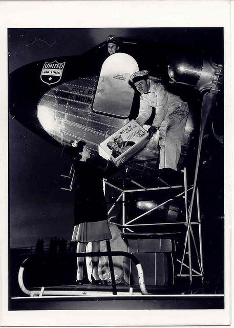 WWII ~ A volunteer helps load into an airplane a USO Care Package destined for a lucky overseas service member in Des Moines, Iowa, 1940s.