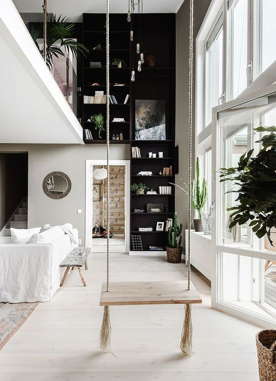 Bohemian living room decor with black and white, a dramatic wall of shelves, and rustic swing. #livingroom #blackandwhite #bohemian #decorinspiration #swing #indoorswing #blackwalls