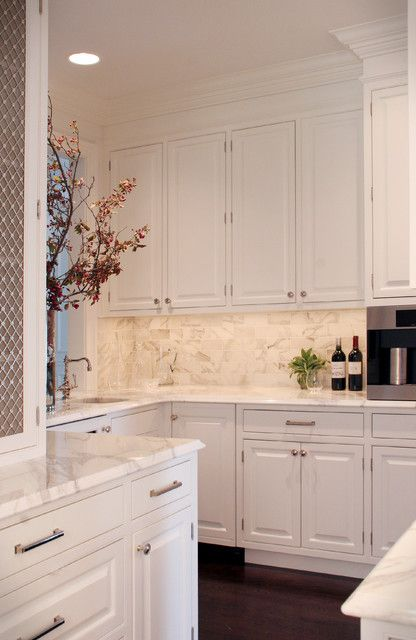 Inspiration for a normal u-shaped kitchen in Cleveland with wood countertops, raised-panel cabinets, white cabinets, stone slab backsplash, white backsplash and paneled appliances.