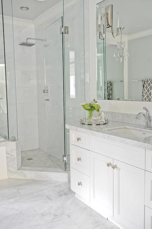 Elegant bathroom features a white vanity fitted with an angled cabinet to make room for a corner shower topped with gray marble under an inset mirror lined with polished nickel sconces.