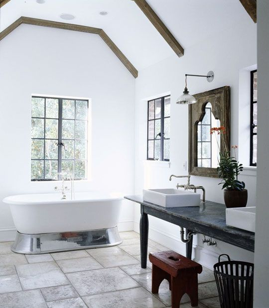 Rectangular sinks complement the floor tiles and shapely mirrors above in this bath - Traditional Home®: