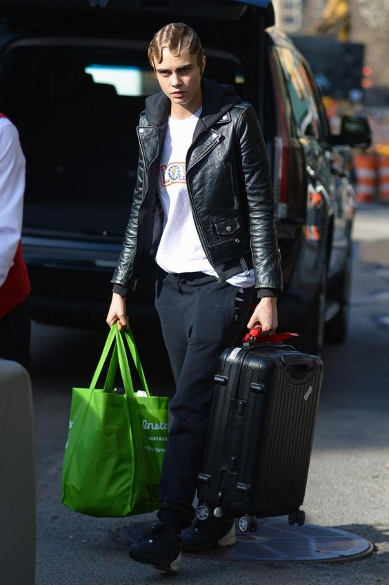 Cara Delevingne wearing Chanel Calfskin & Neoprene Sneakers, Saint Laurent Classic Biker Jacket and Kutula Black Tracksuit Bottoms