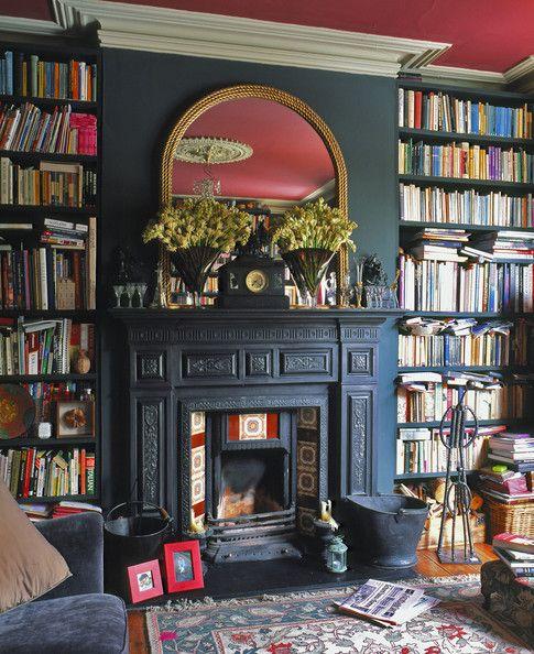 Dark walls, dark book case round fireplace