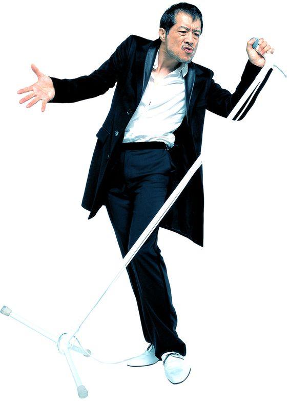 白いシャツに黒いジャケットを着て白いスタンドマイクを握っている矢沢永吉の画像