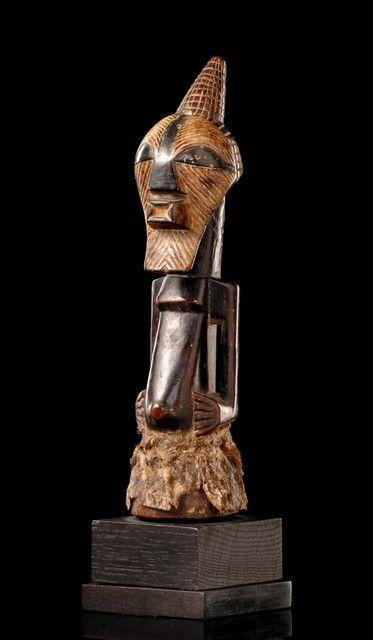 """Kifwebe power figure D. R. Kongo, Songe  Holz, schwarzbraune Glanzpatina, Kaolin,  der Unterkörper vollständig eingehüllt in einen Schurz aus Tierhaut, darüber ein langer Oberkörper mit eckigen Schultern, der frei gearbeitete, angewinkelte Arme entsendet, die Hände ruhen seitlich des leicht hervortretenden Bauchnabels, bekrönt von einem Kopf, der in Form einer """"kifwebe""""-Maske gestaltet ist und von einem geschnitzten Scheitelhorn bekrönt wird  Provenienz Jan Lundberg, Malmö, Sweden"""
