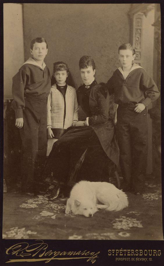 Maria Feodorovna, Imperatriz da Rússia com seus três filhos mais velhos Czarevich Nicolau, mais tarde, Nicholas II, Grão-Duque George Alexandrovich e Grã-Duquesa Xenia Alexandrovna. Maria Feodorovna está sentado no centro do grupo com a grã-duquesa Xenia em pé ao lado dela para a esquerda. Czarevich Nicholas está de pé para o lado esquerdo e Grão-duque George para a extrema direita. Ambos estão vestindo ternos de marinheiro. Um cão está deitado no chão na frente. Cerca de 1883.