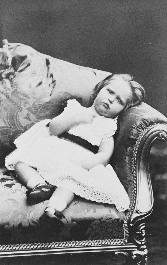 A jovem princesa Alix de Hesse está sentada, encostada na almofada no canto da cadeira / sofá; ela olha para a câmera. Usa vestido de manga curta; meias curtas, sapatos. Dezembro de 1873.