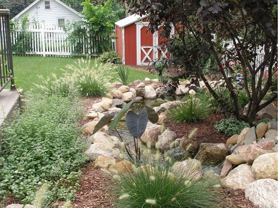 Native grasses and perennials line the flowing water feature.