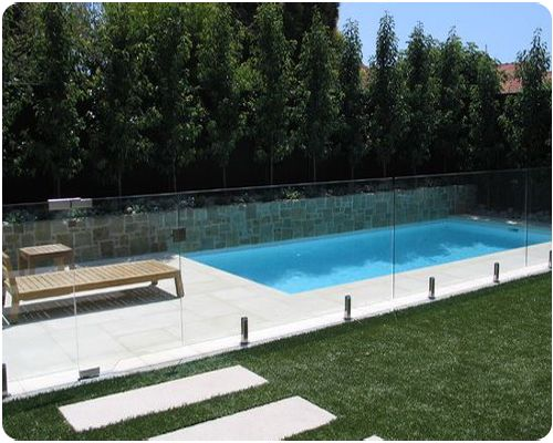 Combining frameless glass fencing with stone retaining for Designer glass pool fencing