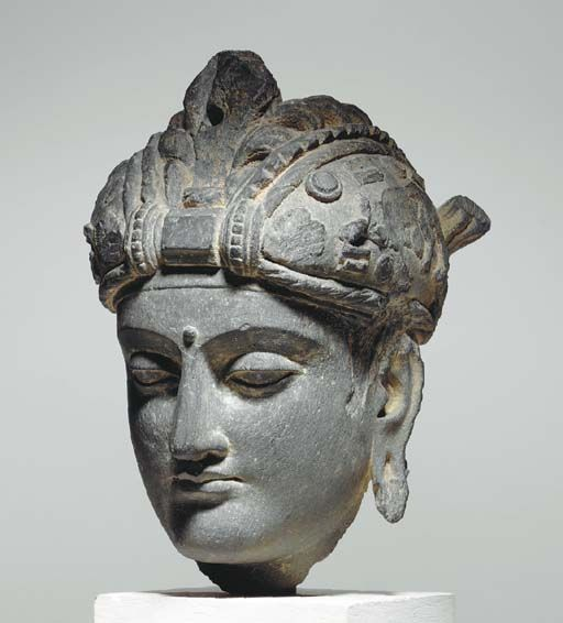 A Gray Schist Head of a Bodhisattva* GANDHARA, 2ND/3RD CENTURY. Gandhara is the ancient name of a region in northwest Pakistan bounded on the west by the Hindu Kush mountain range and to the north by the foothills of the Himalayas.