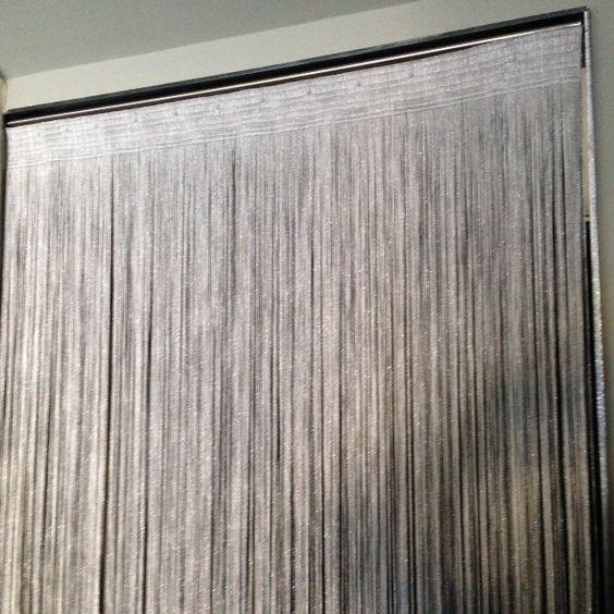 Tenda verticale a fili color nero- argento, cucite su fettuccia con velcro applicate a infisso.