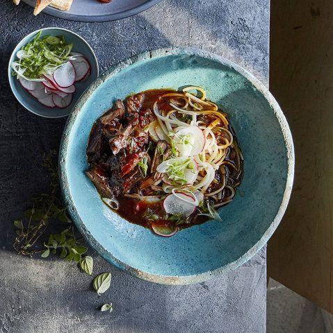 Slow-Cooker Asian Shredded Beef | If you're feeling restless for travel but short on funds, why not try and do a little culinary exploring with your slow cooker instead? This tangy Asian-inspired noodle bowl tastes better than any take out and comes together in a snap: simply mix some beef broth with a few sauces—sweet hoisin, umami-rich soy sauce, and rice vinegar—and stir in some ginger and crushed red pepper. Then add the beef, cover, and cook on low while you get on with your…