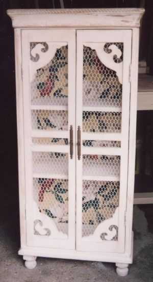 Revamped cupboard with fretwork and fabric added to new paint job.