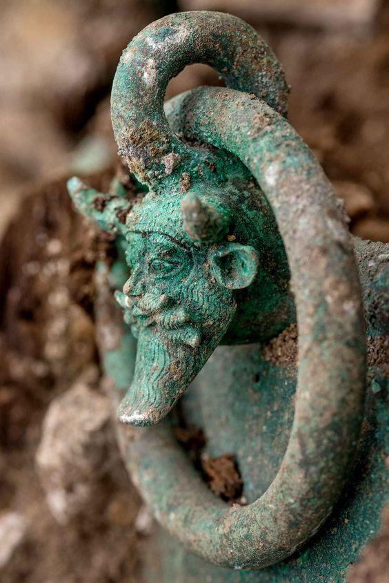 Sur le chaudron, une des anses décorées d'une tête du dieu Acheloos.