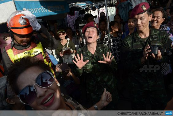 THAILAND, Bangkok : Thai soldiers (C) dance with residents at a military event organised to 'return happiness to the people' at Victory Monument, the site of recent anti-coup rallies in Bangkok on June 4, 2014. Thailand's military staged a coup on May 22, banned all public protests and imposed martial law, controls on the media and a night-time curfew. AFP PHOTO / Christophe ARCHAMBAULT