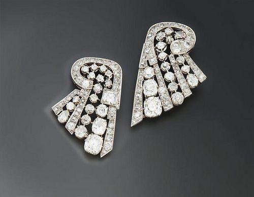 Adjugé 17 200 euros par Azur Enchères à Cannes le 28 mars 2014 - Deux clips de revers formant paire, en platine et or gris ajouré, pavés de diamants de taille ancienne, les plus importants de forme coussin (poids des diamants principaux : environ 10 ct) - Travail français vers 1930 - Poids brut : 39 g