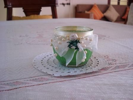 Hand poured green candle in a glass container decorated with rose, ribbons and pearls
