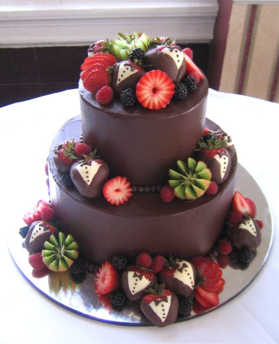 "awesome chocolate groom's cake with chocolate covered ""tuxedo"" strawberries and kiwi."