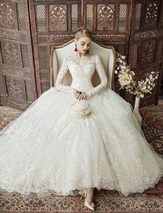 Oh My Lace! This Eileen Couture wedding dress is filled with exquisitely feminine details perfect for the vintage bride! notice details...wingback chair, shoes, sleeves, earrings, rug, screen, does not have flowers in hand but flowers in image, hands are still occupied by prop. Lovely photograph nice job team!: