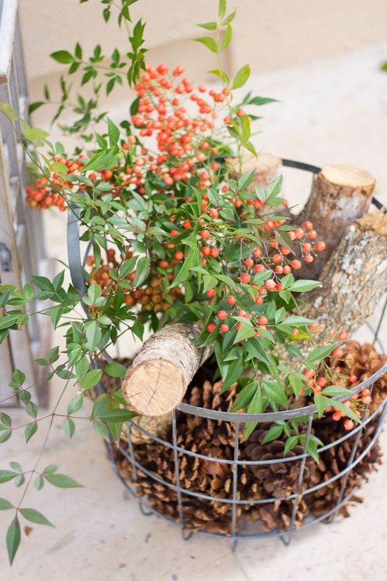 Christmas basket filled with pine cones, logs, and berries
